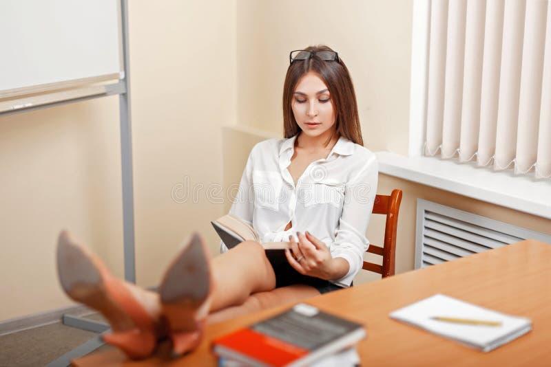 Mooie jonge vrouw die en een boek ontspannen lezen stock afbeeldingen