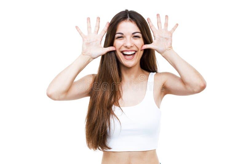 Mooie jonge vrouw die en grappig gezicht over witte achtergrond maken gekscheren stock afbeelding
