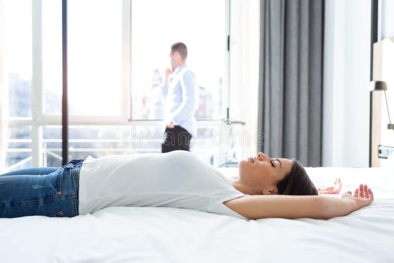 Mooie jonge vrouw die en op bed in hotelruimte liggen ontspannen stock fotografie