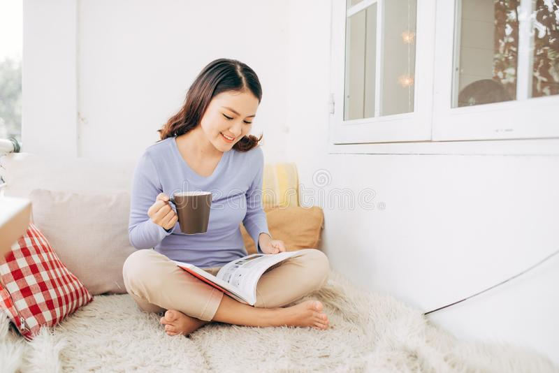 Mooie jonge vrouw die en op een buitenbed op een tuin van het huisterras en tijdschriften ontspannen bepalen terwijl lezen royalty-vrije stock afbeelding
