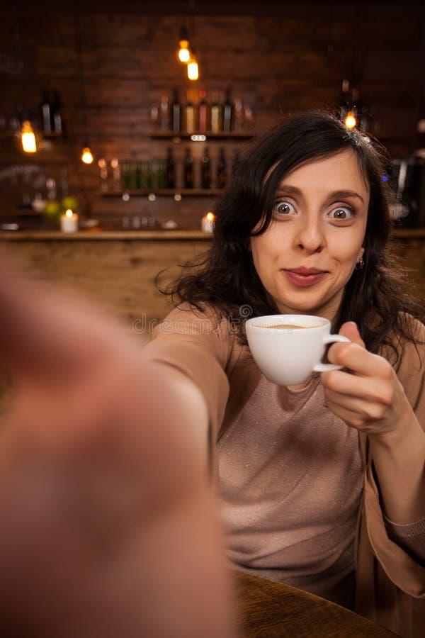 Mooie jonge vrouw die en smarthphone glimlachen gebruiken om een zelf-portret in een koffiewinkel te maken stock foto