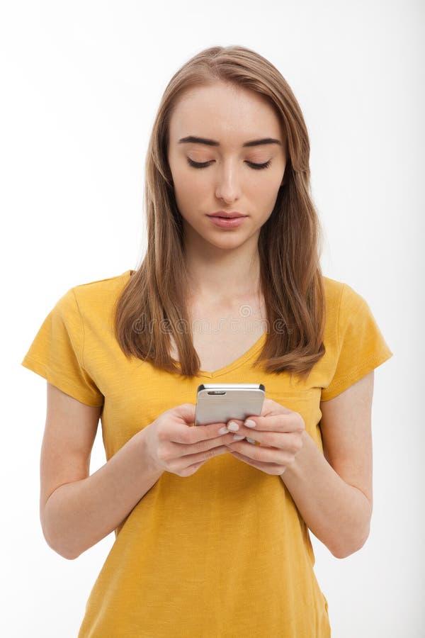 Mooie jonge vrouw die gele lege malplaatjet-shirt dragen en op smartphone op wit texting Vopyruimte en spot omhoog stock foto's