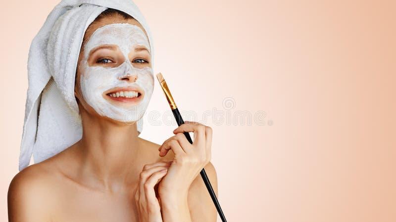 Mooie jonge vrouw die gezichtsmasker op haar gezicht met borstel toepassen Huidzorg en behandeling, kuuroord, natuurlijke schoonh royalty-vrije stock afbeelding