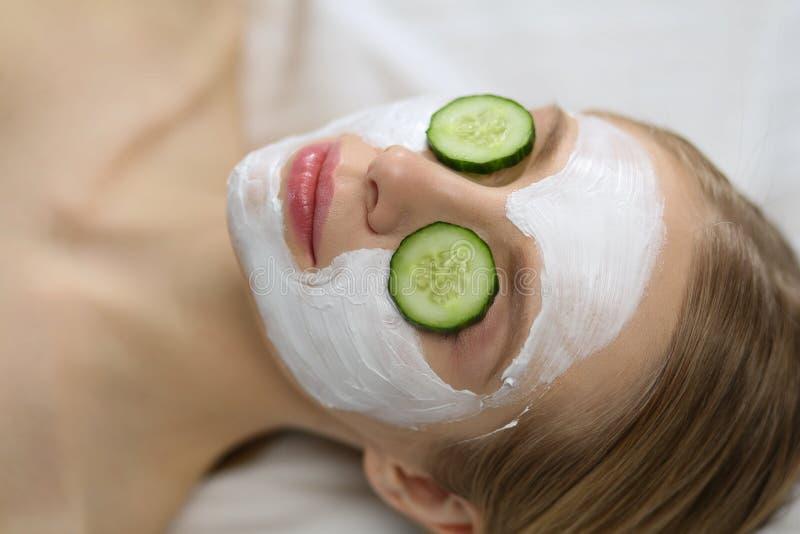 Mooie jonge vrouw die gezichtsmasker van komkommer in schoonheidssalon ontvangen stock foto