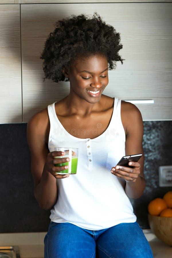 Mooie jonge vrouw die groen detoxsap drinken en haar mobiele telefoon thuis met behulp van royalty-vrije stock fotografie