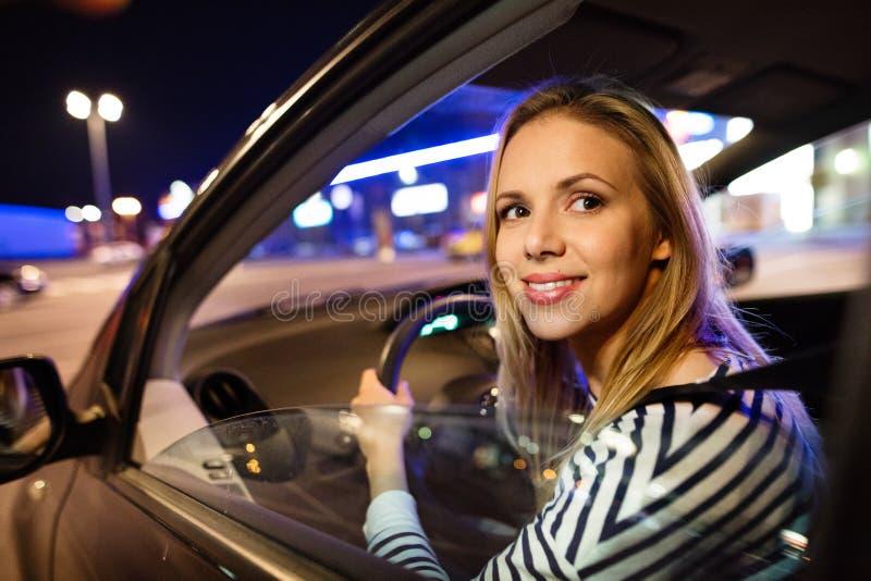 Mooie jonge vrouw die haar auto drijven bij nacht stock fotografie
