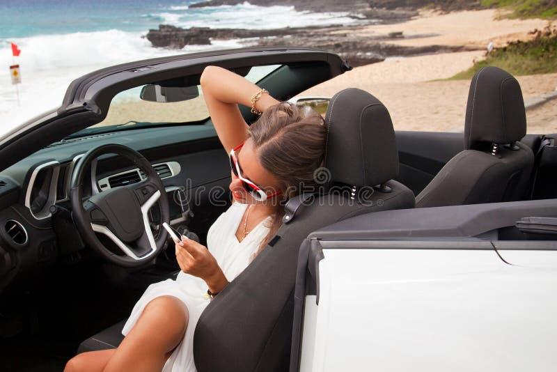 Mooie jonge vrouw die in haar auto rusten royalty-vrije stock afbeelding