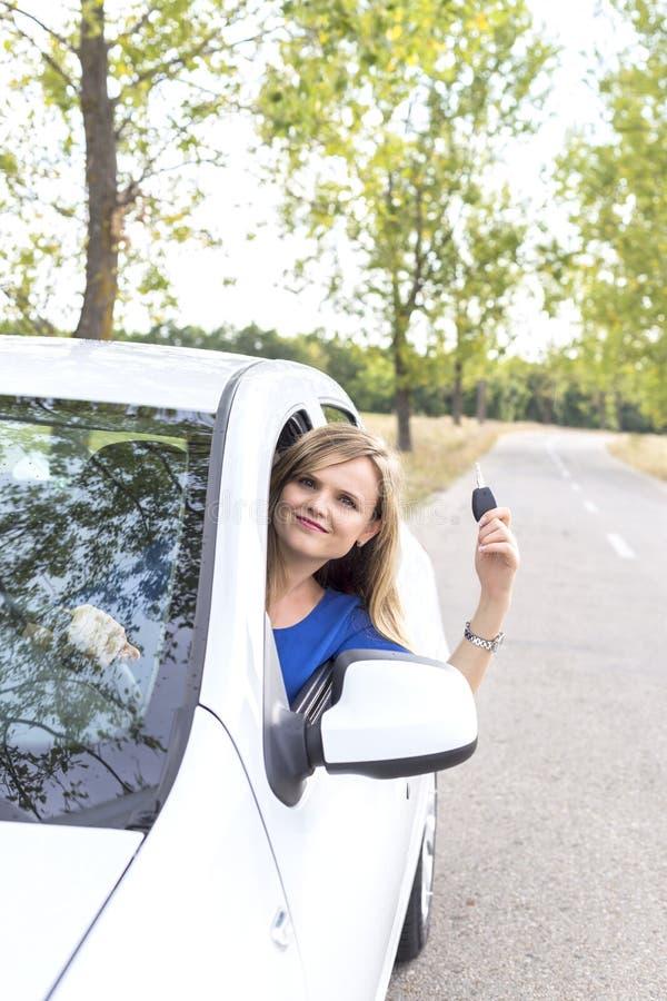 Mooie jonge vrouw die haar autosleutels tonen stock fotografie