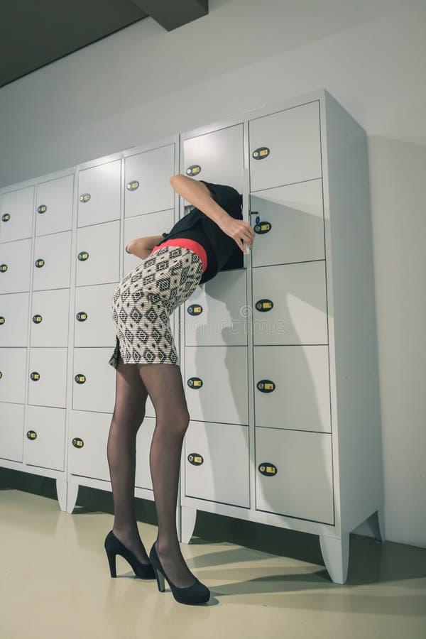 Mooie jonge vrouw die haar hoofd in een kast zetten royalty-vrije stock foto's
