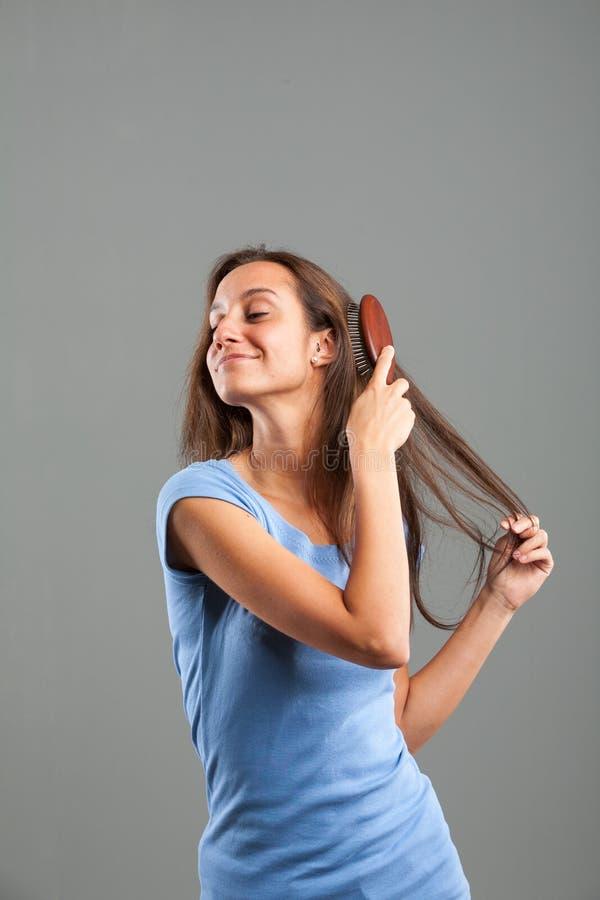 Mooie jonge vrouw die haar lang bruin haar borstelen royalty-vrije stock afbeelding