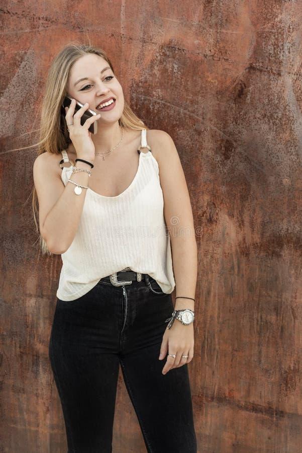 Mooie jonge vrouw die haar mobiele telefoon met behulp van stock afbeelding