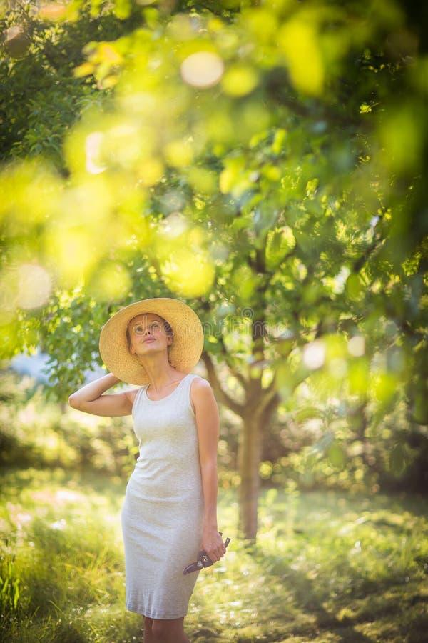 Mooie, jonge vrouw die in haar tuin tuinieren royalty-vrije stock afbeeldingen