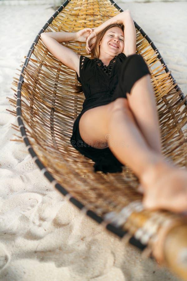 Mooie jonge vrouw die in hangmat op het zandige strand en de vrolijke het glimlachen hoogste mening liggen in camera royalty-vrije stock foto's