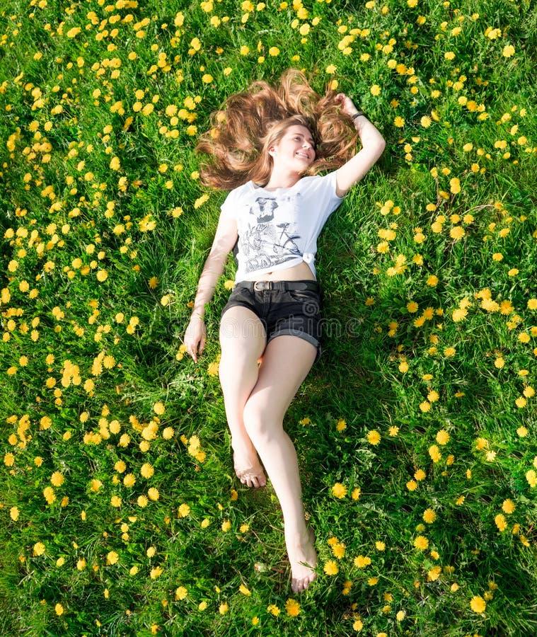 Mooie jonge vrouw die in het gras ligt royalty-vrije stock afbeelding