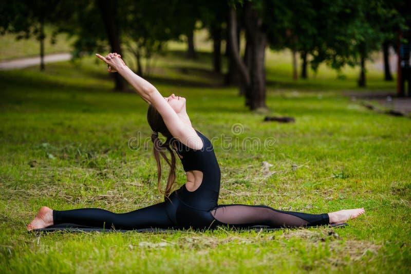 Mooie jonge vrouw die het ontspannen doen en oefeningen in het park uitrekken royalty-vrije stock afbeelding