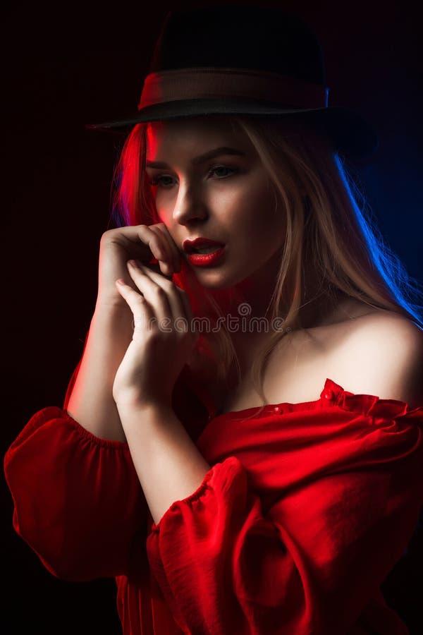 Mooie jonge vrouw die het rode blouse en hoeden stellen in de elft dragen stock afbeelding