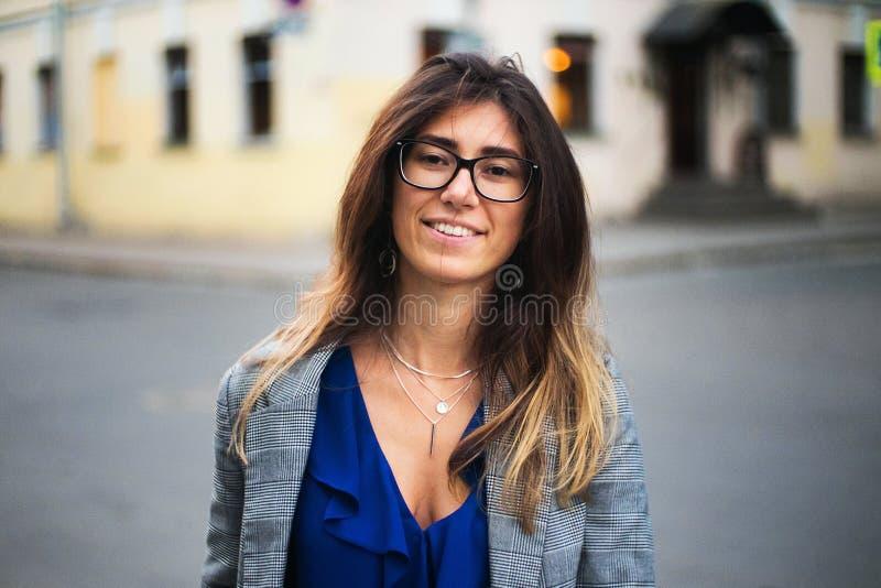 Mooie jonge vrouw die het vrolijke lopen op de straat op een zonnige dag, toevallig mooi meisje bij de stad glimlachen stock afbeelding