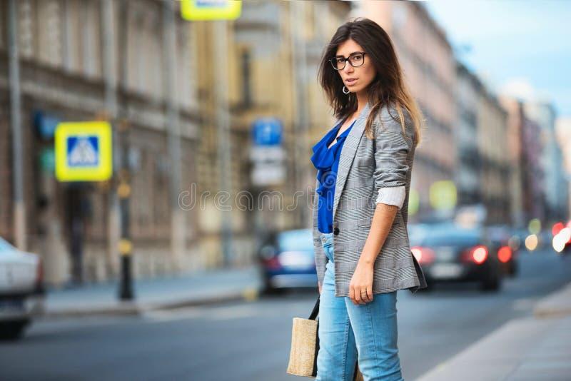 Mooie jonge vrouw die het vrolijke lopen op de straat op een zonnige dag, toevallig mooi meisje bij de stad glimlachen stock foto