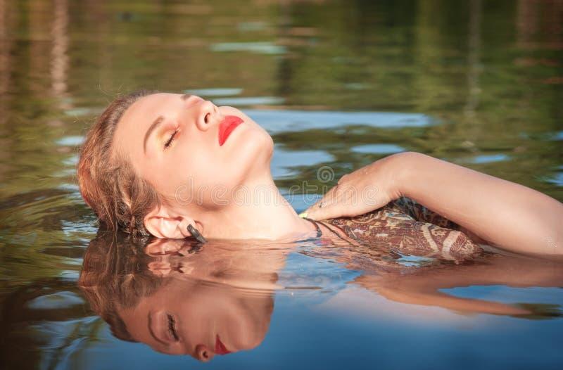 Mooie jonge vrouw die in het water liggen royalty-vrije stock afbeeldingen