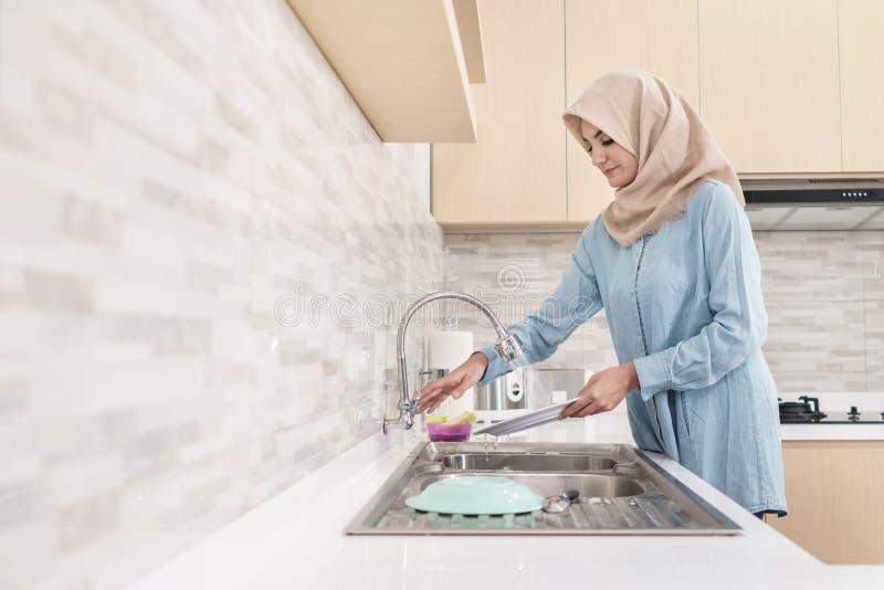 Mooie jonge vrouw die hijab wassend de schotels dragen stock foto