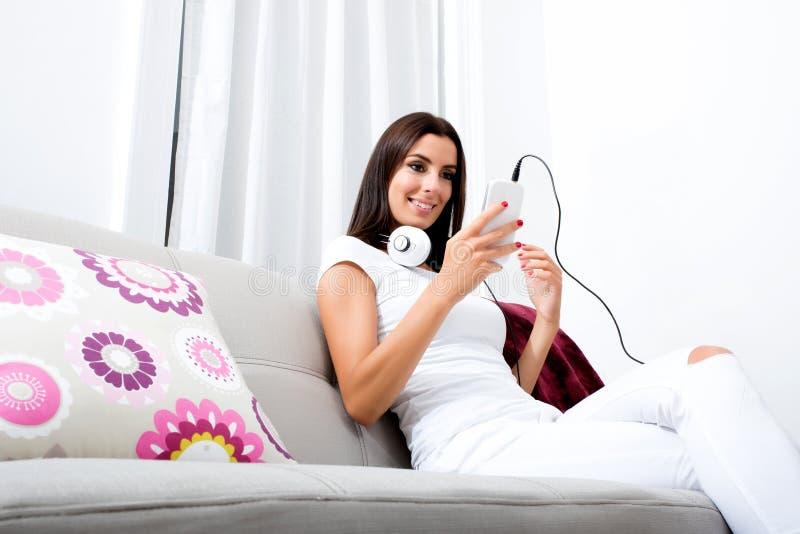 Mooie jonge vrouw die in hoofdtelefoons aan muziek luisteren royalty-vrije stock fotografie