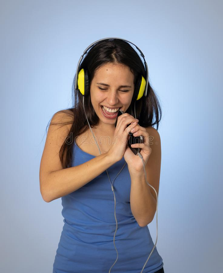Mooie jonge vrouw die in hoofdtelefoons aan muziek op mobiele en telefoon luisteren die dansen zingen stock foto