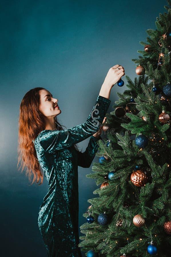 Mooie jonge vrouw die Kerstboom, het glimlachen verfraaien Het concept van het nieuwjaar Huis en familiewarmte Groene luxe, blauw royalty-vrije stock foto's