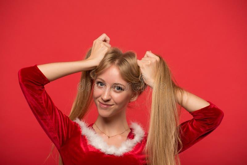 Mooie jonge vrouw die in Kerstmankostuum met een bundel die van haar lang zijdeachtig haar spelen, camera op rode achtergrond bek stock afbeeldingen