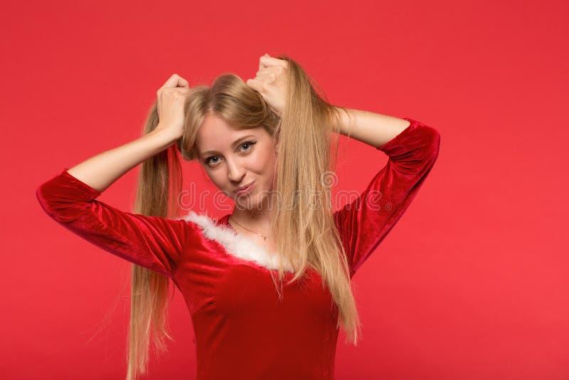 Mooie jonge vrouw die in Kerstmankostuum met een bundel die van haar lang zijdeachtig haar spelen, camera op rode achtergrond bek stock afbeelding