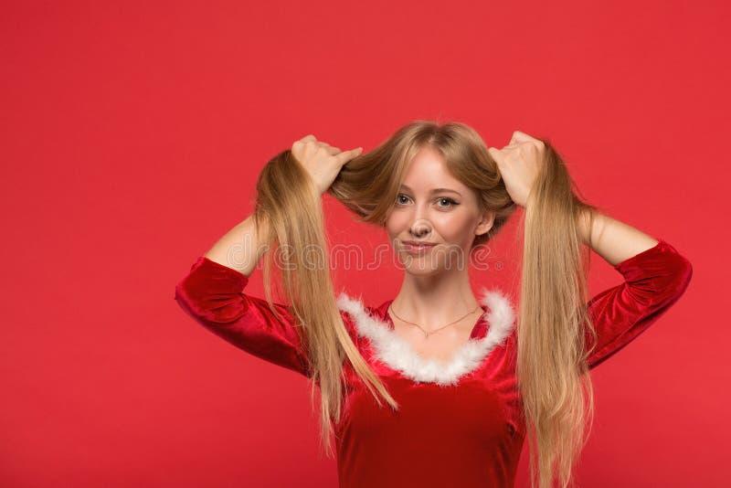 Mooie jonge vrouw die in Kerstmankostuum met een bundel die van haar lang zijdeachtig haar spelen, camera op rode achtergrond bek stock foto's