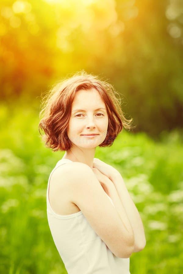 Mooie jonge vrouw die koesteren bij de zomerzonsondergang royalty-vrije stock afbeelding