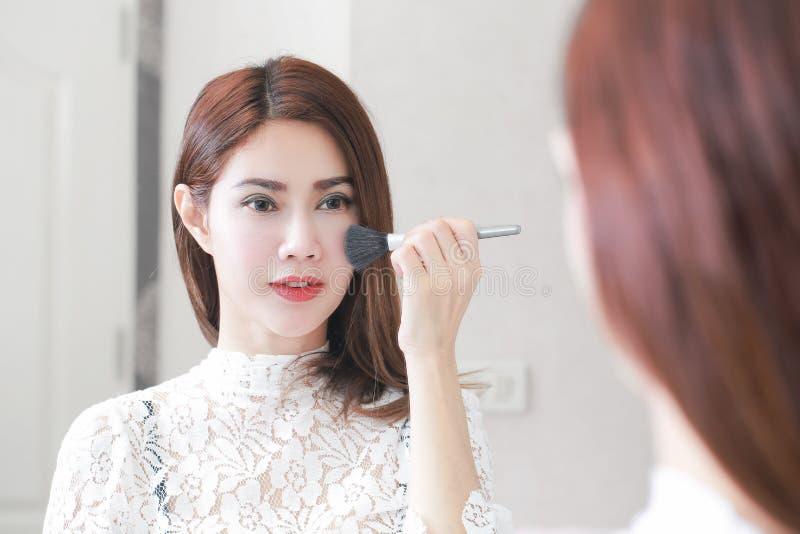 Mooie jonge vrouw die kosmetisch poeder op haar gezicht toepassen met royalty-vrije stock afbeelding