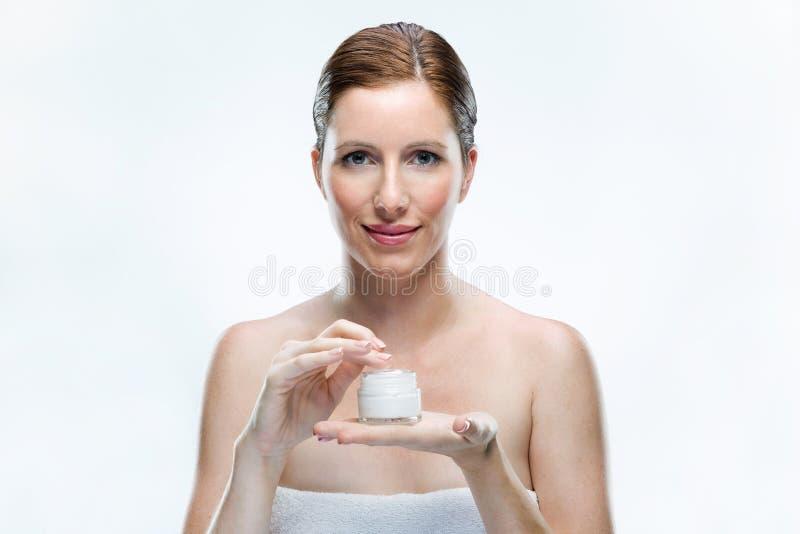 Mooie jonge vrouw die kosmetische room op gezicht over witte achtergrond toepassen royalty-vrije stock afbeeldingen