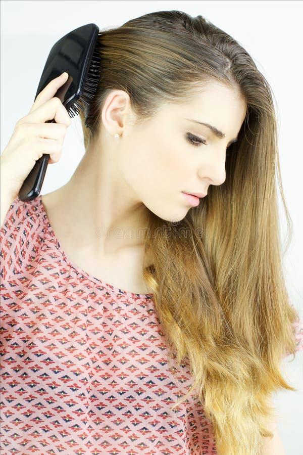 Mooie jonge vrouw die lang blondehaar borstelen stock afbeelding