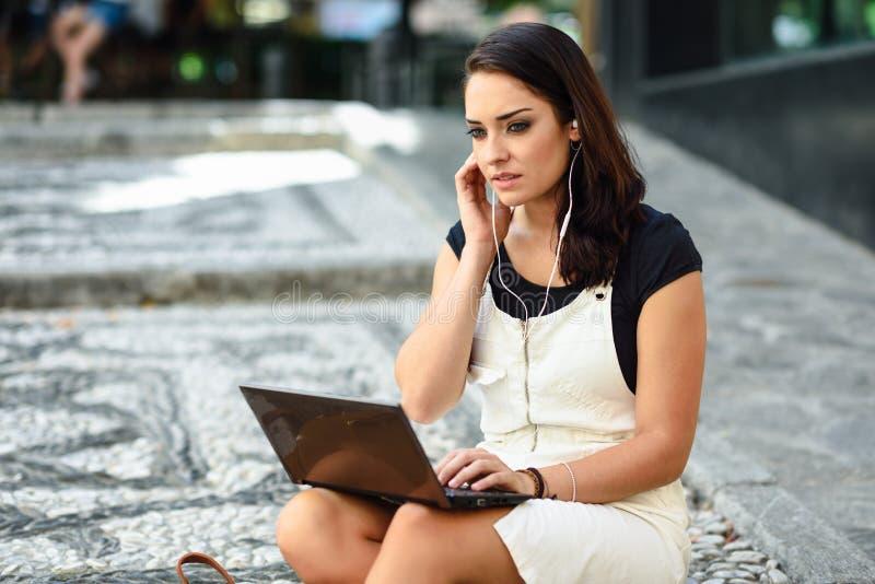 Mooie jonge vrouw die laptop computerzitting op stedelijke stappen gebruiken Onderneemster die vrijetijdskleding dragen die in op stock foto