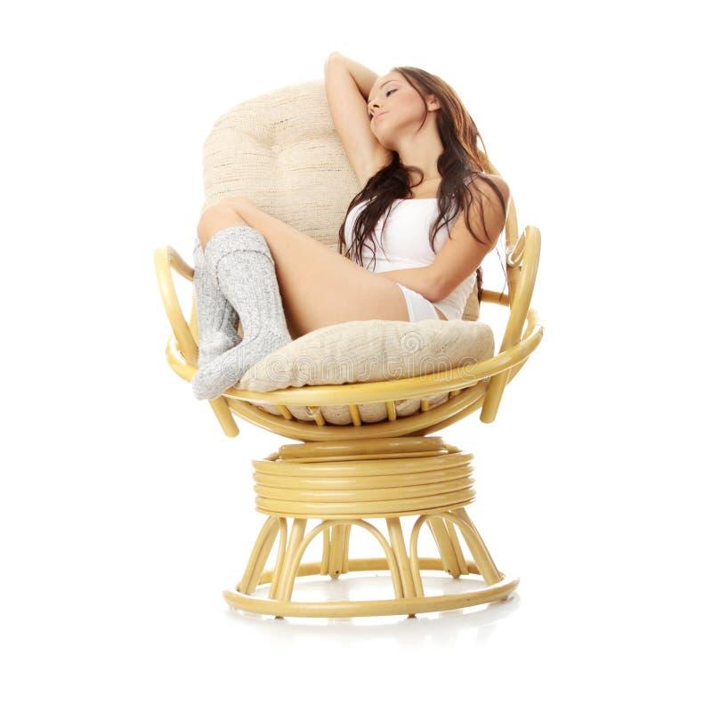 Mooie jonge vrouw die in leunstoel rust. royalty-vrije stock fotografie