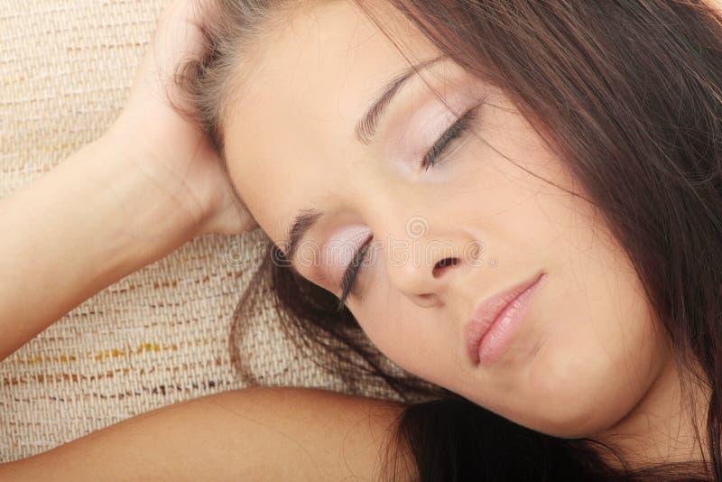 Mooie jonge vrouw die in leunstoel rust. stock afbeelding