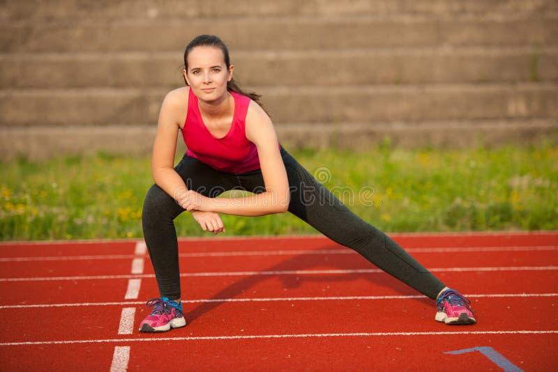 Mooie jonge vrouw die longe stap op atletisch spoor doen stock foto