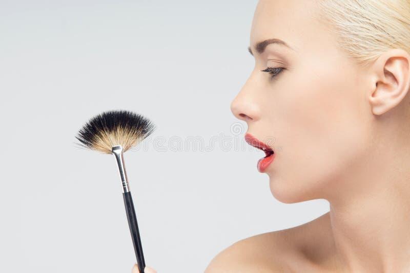 Mooie Jonge Vrouw die Make-up met Borstel toepassen royalty-vrije stock afbeelding