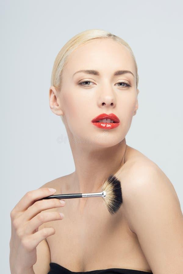 Mooie Jonge Vrouw die Make-up met Borstel toepassen stock afbeelding