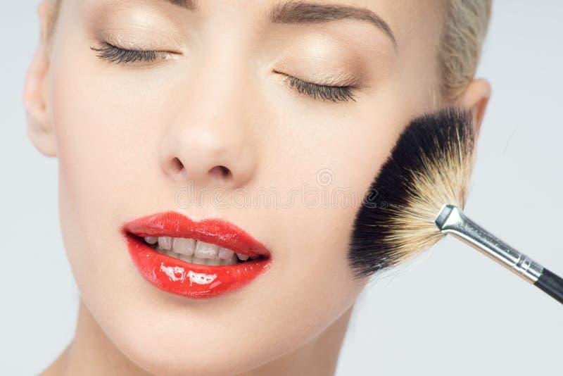 Mooie Jonge Vrouw die Make-up met Borstel toepassen stock fotografie