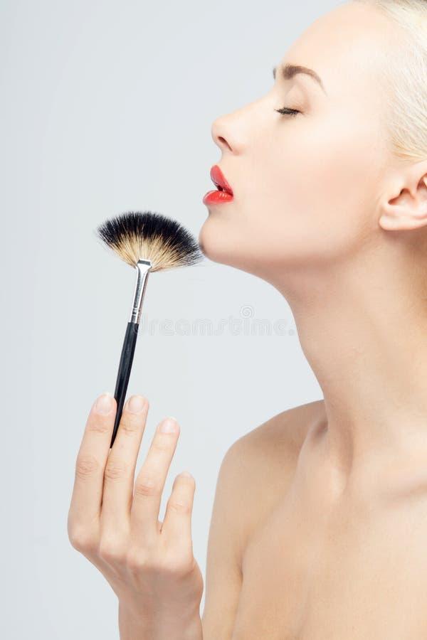 Mooie Jonge Vrouw die Make-up met Borstel toepassen stock afbeeldingen