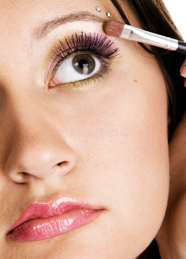 Mooie jonge vrouw die make-up toepast stock foto