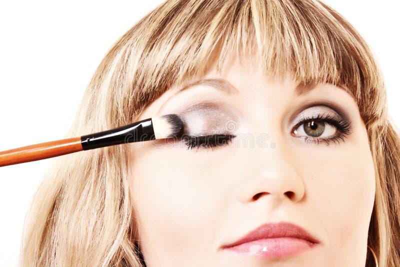 Mooie jonge vrouw die make-up toepast royalty-vrije stock foto's