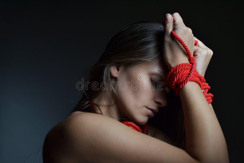 Mooie jonge vrouw die met de rode kabel wordt gebonden stock afbeeldingen