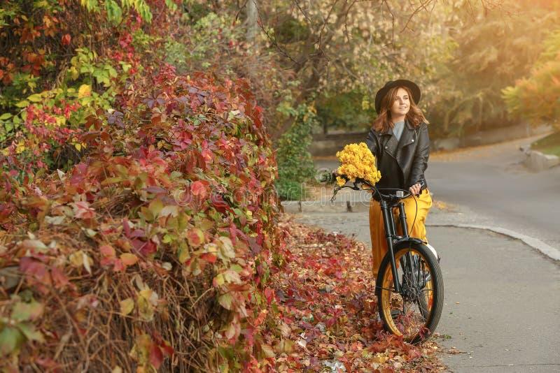 Mooie jonge vrouw die met fiets gele bloemen in openlucht houden royalty-vrije stock foto's