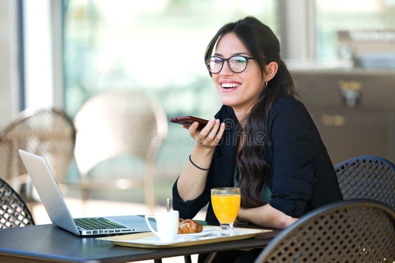 Mooie jonge vrouw die met haar mobiele telefoon spreken terwijl het hebben van ontbijt terwijl het werken met haar laptop in een  stock foto