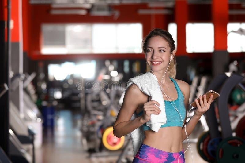 Mooie jonge vrouw die met handdoek aan muziek in gymnastiek luisteren royalty-vrije stock afbeeldingen