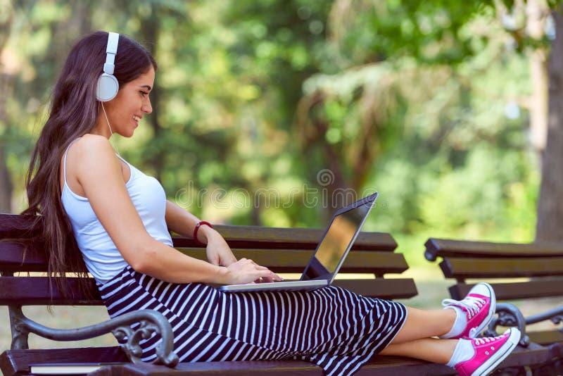 Mooie jonge vrouw die met hoofdtelefoons op bank in het park zitten, die laptop computer met behulp van royalty-vrije stock foto's