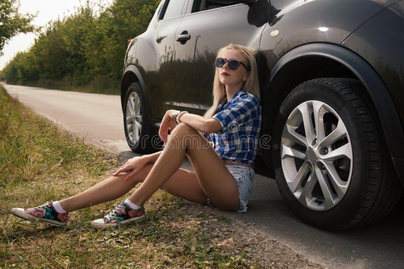 Mooie jonge vrouw die met lang blond haar in borrels op de weg zitten die op de auto op de zonsondergang leunen stock afbeeldingen